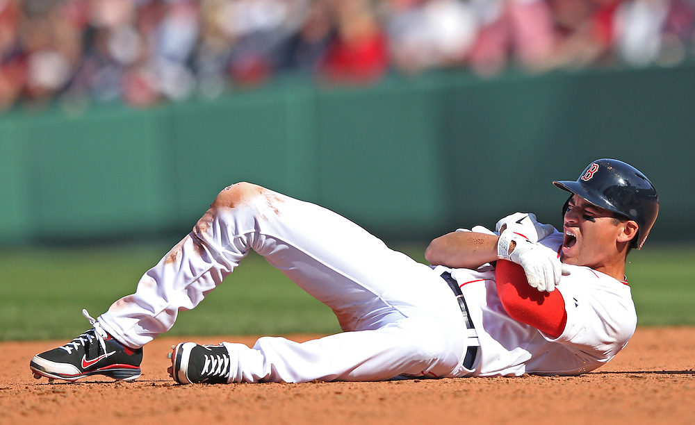The Boston Red Sox' Jacoby Ellsbury winces in pain after injuring himself during a collision with the Tampa Bay Rays' short stop Reid Brignac in the fourth inning at Fenway Park in Boston, Massachusetts, USA on 13 April 2012. The game marks the season home opener for the Red Sox who have won just one game so far this year.