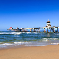 Photo of Huntington Beach Pier in Orange County California. Huntington Beach Pier is a registered historic place.  Huntington Beach is also known as Surf City USA and is a seaside beach city along the Pacific Ocean in Southern California.