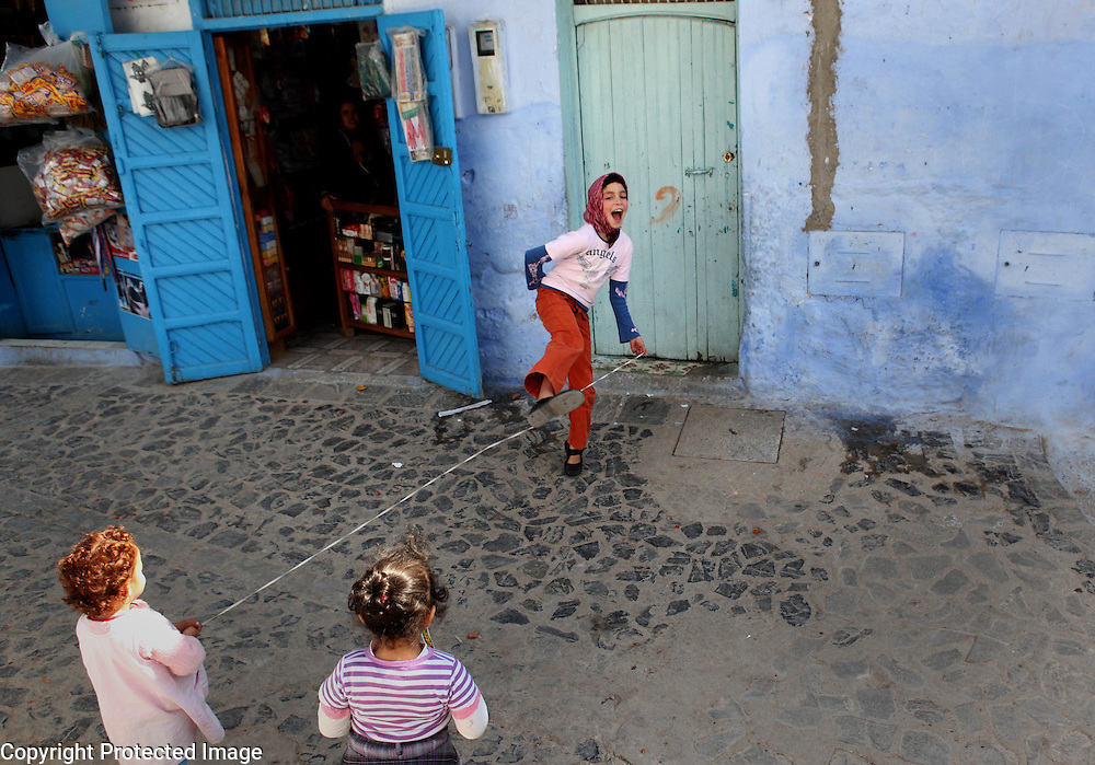 "A girl laughs while she plays a skipping game with some friends in Chefchaouen, Morocco, whose ""medina"" (old city) is famous for its striking blue walls."