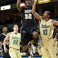 Central Florida guard/forward Isaiah Sykes (32) drives to the basket against Anthony Crater (10) during the NCAA basketball game against the USF Bulls at the UCF Arena on November 18, 2010 in Orlando, Florida. UCF won the game 65-59. (AP Photo/Alex Menendez)