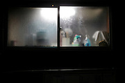 frosted kitchen window with water damp and cleaning products during night