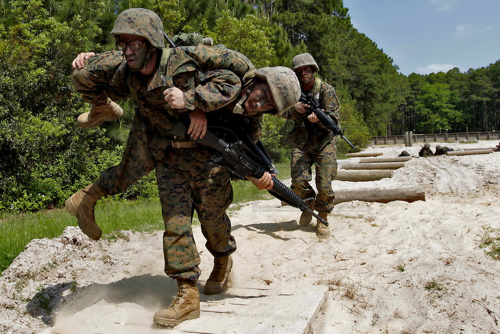 A recruit carries his simulated wounded colleague away from the battlefield during the Crucible.  The Crucible is A 52 hour final test in their recruit training and represents the culmination of all of the skills and knowledge a marine should possess.  Marine Corps Recruit Depot at Parris Island in South Carolina is where all male recruits living east of the Mississippi River and all female recruits from all over the US receive their arduous twelve week training in their quest to become marines. Even though there are two current active wars and a weak economy, recruitment has not been effected.  Actually, recruiting numbers have increased, with more young men and women looking toward the military for answers.