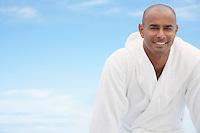 Man in bathrobe smiling half length