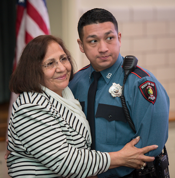 Jose Rangel, right, gets a hug from his mother after receiving his badge during a swearing-in ceremony for new officers at the Houston ISD Police Department, March 3, 2014.