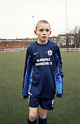 Young boy wearing football uniform.