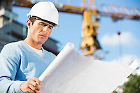 Male architect reviewing blueprint at construction site