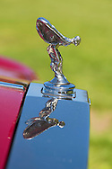 Westbury, New York, USA. June 12, 2016.  Flying Lady chrome hood ornament is reflected atop grille of 1985 red Rolls Royce Silver Spur, owned by John Shorter, on display at the Antique and Collectible Auto Show at the 50th Annual Spring Meet at Old Westbury Gardens, in the Gold Coast of Long Island, and sponsored by Greater New York Region, GNYR, Antique Automobile Club of America, AACA. Participating vehicles in the judged show included hundreds of domestic and foreign, antique, classic, collectible, and modern cars.