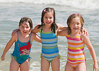 Cousins take a photo together on the beach. The girls are age 4 to 7.