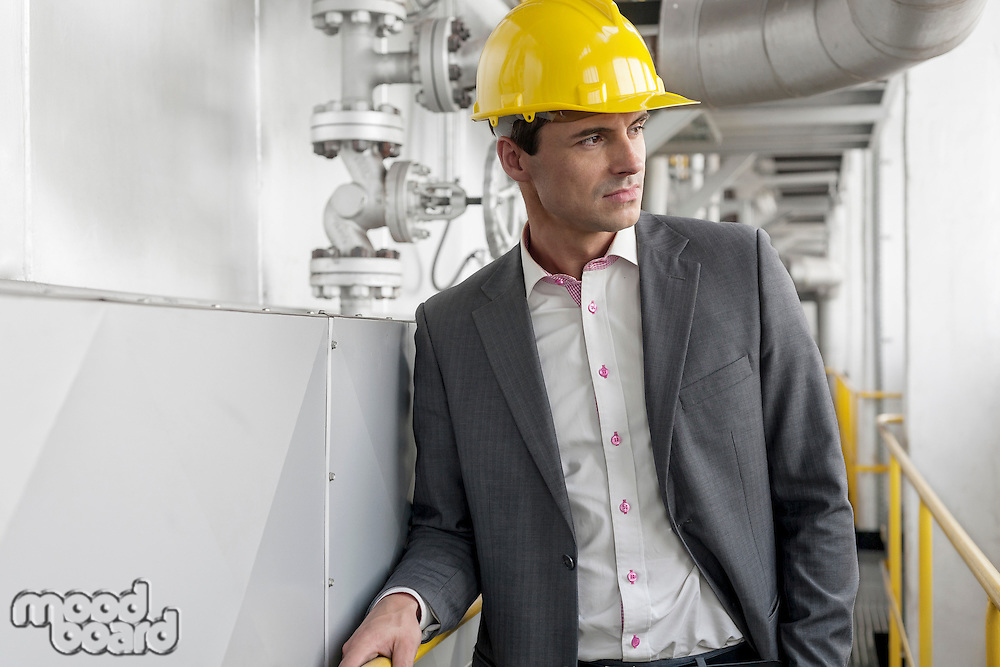Young male architect in hard hat looking away at industry