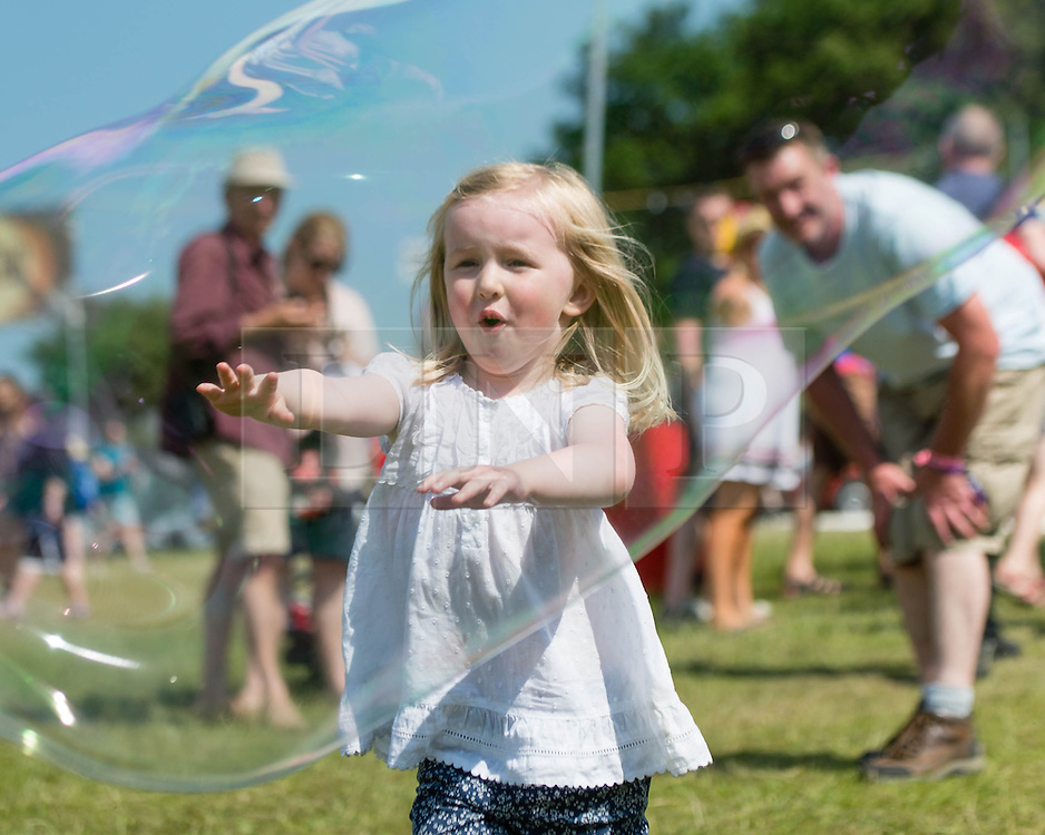 © Licensed to London News Pictures. 13/06/2014. Isle of Wight, UK.   A young girl chases giant bubbles in the hot sun Isle of Wight Festival 2014.   The Isle of Wight festival is an annual music festival that takes place on the Isle of Wight. Photo credit : Richard Isaac/LNP