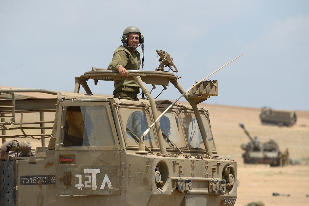 UNSPECIFIED, ISRAEL - JULY 19, 2014: An Israeli soldier stands atop an APC in an army deployment area near Israel's border with the Gaza Strip, on July 19, 2014, on the second day of Israeli ground invasion into Gaza Strip in order to destroy terror tunnels infrastructure. Photo by Gili Yaari