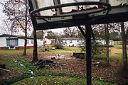 "BUTLER COUNTY, AL – DECEMBER 7, 2017: A basketball goal is surrounded on three sides by hand-dug trenches that carry raw sewage to a nearby creek, feeding the larger Pigeon Creek situated south of Butler County. The makeshift basketball court is used regularly by children ages five through eighteen.<br /> <br /> Inadequate sewage treatment has plagued Alabama's poor Black Belt community for decades, often leading to problems of overflow and contamination of the area's water supply. In some areas, improper sewage treatment has even put the population at risk of diseases long believed to be extinct in the United States. With failing or absent municipal sewer service in Lowndes and Butler counties, many families choose to live with open systems made from PVC pipe. This ""straight pipe"" method carries raw sewage away from the home as far as gravity allows, often directing it into nearby streams or even onto open land just feet from the front door. Private septic tanks are prohibitively expensive for most, but even those who use them complain of sewage backing up into their homes during heavy rains, due to the region's chalky clay soil. As a cheap fix, trenches are often dug by residents for temporary relief, diverting raw sewage away from their homes and into nearby creeks."