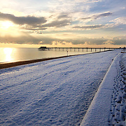 Deal pebble beach covered in a sprinkling of snow.
