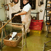 A baker works in in his show with water on a day of exceptional High Tide in Venice with water above 140cm covering more than 50% ot town Marco Secchi /xianpix<br /> msecchi@gmail.com