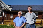 University Park, Maryland - May 04, 2015: Don Monroe, left, and David Brosch, right, stand in front of a 22 kilowatt solar electric array atop the roof of the University Park Church of the Brethren in University Park, Maryland Monday May 4th, 2015. Monroe is chair of property commission for the church and the middle man between the local power utility PEPCO and University Park Community Solar, LLC, the 35 member corporation that owns the solar panels. Brosch is president of the University Park Community Solar, LLC. The solar panels on top of the church produces an estimated 25% more energy than the church needs per year. Members of the LLC who helped pay for the solar panels receive dividends based on the money they invested, but no energy. <br /> <br /> CREDIT: Matt Roth