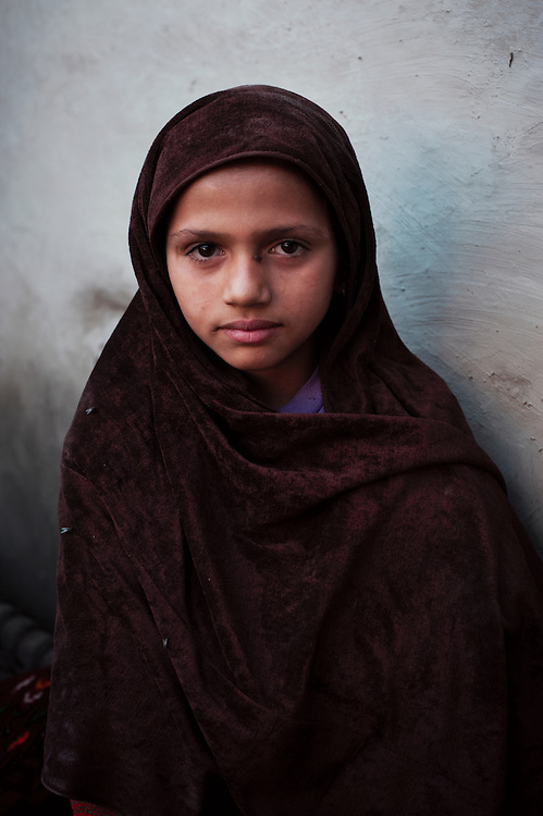 "Pakistan/ Afghan refugees/ Tasleem, 8 years old sits within  her foster parents home in Khazana refugee camp, Peshawar. In 2007 a roof collapsed and killed the childrens parents and they are being cared for by a relative Hamedullah who came to Pakistan 30 years ago from Jalalabad. He would not return back to Afghanistan saying ""We have nothing there."".The camp was established when refugees flooded across the border from Afghanistan during the 1979 Soviet occupation. The refugee camp has a population of 2500 and during the 2010 floods that swept through Pakistan most families were affected. The majority of people rebuilt their houses after the floods with their own resources. The most vulnerable also received support from UNHCR for reconstruction. UNHCR/Sam Phelps/ November 2011 UNHCR/Sam Phelps/ November 2011."