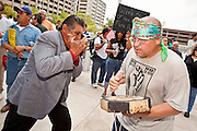 22 JULY 2010 -- PHOENIX, AZ: Julian Estrada (CQ), who says he is the great grandson of the Apache chief Geronimo, and William Robles, from Guadalupe, play harmonica and drums downtown. Both are opposed to 1070. Thousands of people came to the Sandra Day O'Connor United States Courthouse (CQ) in downtown Phoenix Thursday. PHOTO BY JACK KURTZ