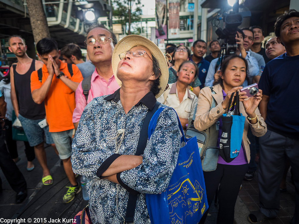 18 AUGUST 2015 - BANGKOK, THAILAND: People on a sidewalk in front of Erawan Shrine in Bangkok look up to the trees around the shrine to see if there is still debris from the explosion in the shrine, including body parts, in the trees. An explosion at Erawan Shrine, a popular tourist attraction and important religious shrine in the heart of the Bangkok shopping district, killed at least 20 people and injured more than 120 others, including foreign tourists, during the Monday evening rush hour. Twelve of the dead were killed at the scene. Thai police said an Improvised Explosive Device (IED) was detonated at 18.55. Police said the bomb was made of more than six pounds of explosives stuffed in a pipe and wrapped with white cloth. Its destructive radius was estimated at 100 meters.     PHOTO BY JACK KURTZ