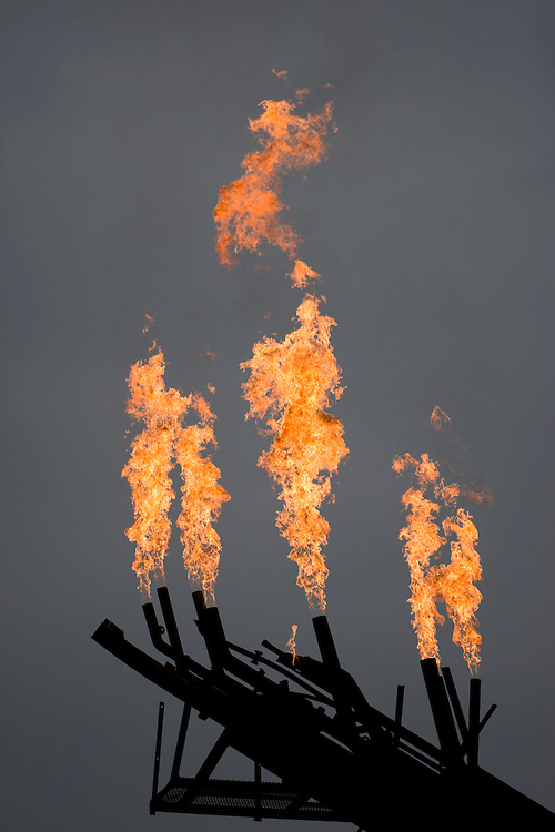 USA, Alaska, Kenai Peninsula, Natural gas flare from offshore oil drilling rig in Cook Inlet on summer evening