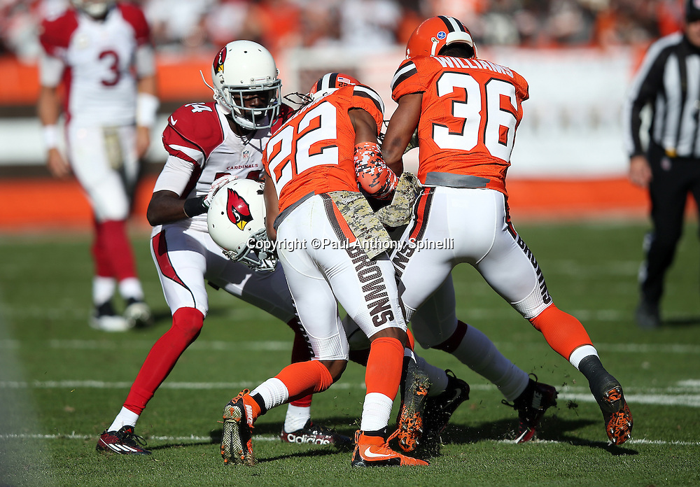 Arizona Cardinals wide receiver J.J. Nelson (14) looks on as Arizona Cardinals running back Chris Johnson (23) gets gang tackled by Cleveland Browns cornerback Tramon Williams (22) and Cleveland Browns free safety K'Waun Williams (36) as Johnson runs the ball in the second quarter during the 2015 week 8 regular season NFL football game against the Cleveland Browns on Sunday, Nov. 1, 2015 in Cleveland. The Cardinals won the game 34-20. (©Paul Anthony Spinelli)