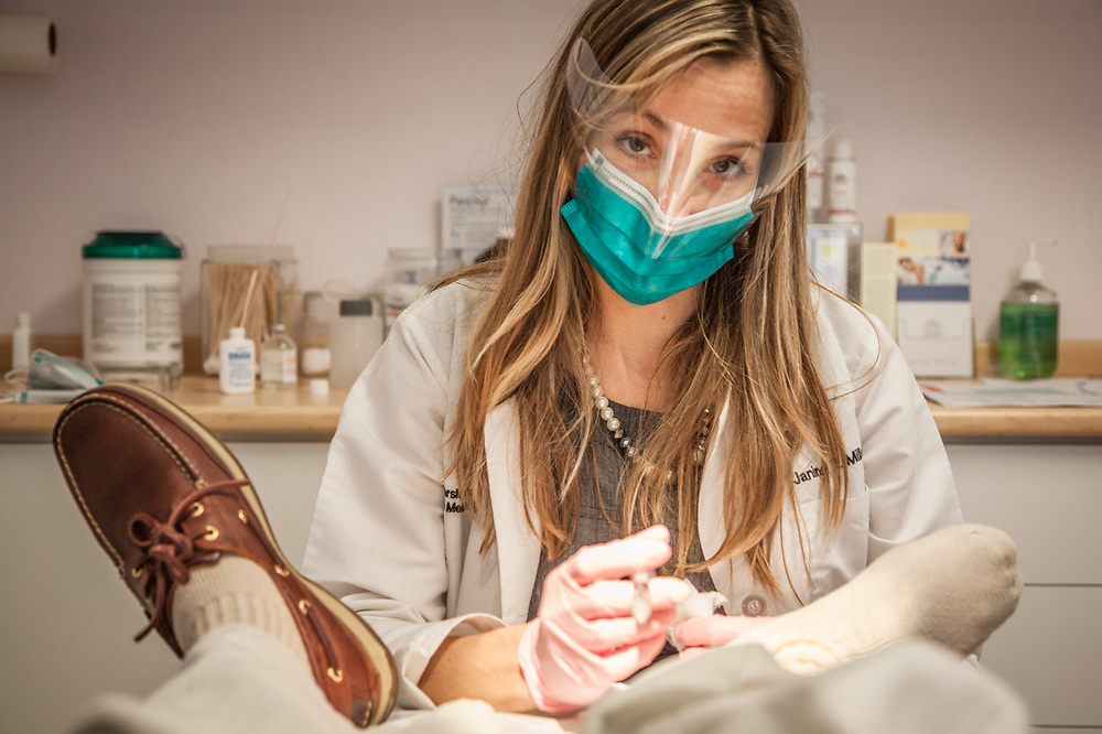 Dr. Janine Miller removes a small growth from the right leg of photographer Clark James Mishler, Anchorage