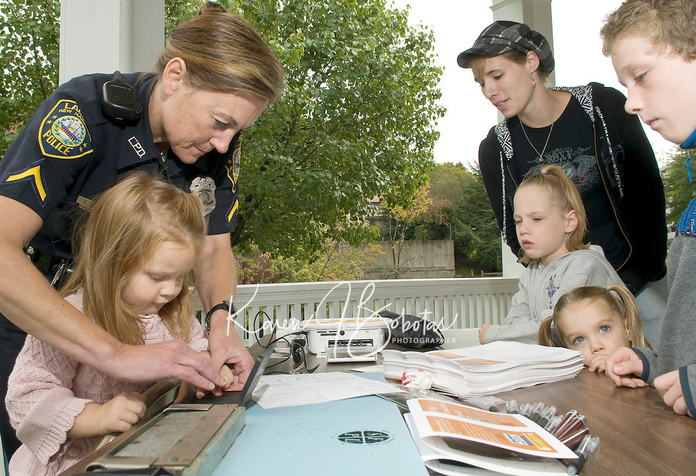 Officer Kathleen Yale fingerprints two year old Kathryn Beane for her Child Identification Booklet while Tara Greenwood, MacKenzie Greenwood, Desiree Daoust and Justin Holmes look on at Laconia Rotary Park Sunday afternoon as part of the Child Safety Day sponsored by the Laconia Rotary Club and Laconia Police and Fire Departments.   (Karen Bobotas/for the Laconia Daily Sun)