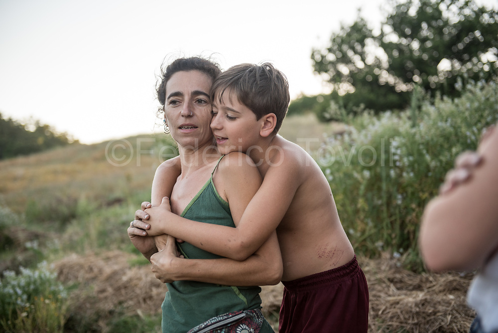 Casa di Paglia. Chianni (PI). Erika Boschetti with her son Leo, at the end of the day in the fields surrounding the straw house.