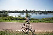 Een man fietst langs de oever van de Maas bij Eijsden. Aan de overkant ligt Belgie.<br /> <br /> A man cycling along the banks of the Meuse at Eijsden. Across the water is Belgium.