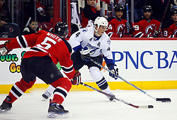March 7, 2008; Newark, NJ, USA; Tampa Bay Lightning center Vincent Lecavalier (4) takes a shot while being defended by New Jersey Devils defenseman Colin White (5) during the first period at the Prudential Center in Newark, NJ.