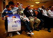 Employees at the Caesar Casino and Hotel attending caucus at their hotel.<br /> <br /> Quincy Smith (7), next to his father Mark, is looking over to the Sanchez family (with the poster) as they are all supporting Obama at the Caucus.