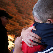 Michael Parrish hugs his mother Joanne Parrish as his father David is seated at a table at Carrabba's Italian Grill. (Jason A. Frizzelle)