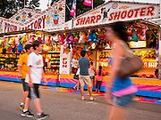 "01 SEPTEMBER 2011 - ST. PAUL, MN:  People walk past the games booths on the midway at the Minnesota State Fair. The Minnesota State Fair is one of the largest state fairs in the United States. It's called ""the Great Minnesota Get Together"" and includes numerous agricultural exhibits, a vast midway with rides and games, horse shows and rodeos. Nearly two million people a year visit the fair, which is located in St. Paul.  PHOTO BY JACK KURTZ"