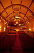 A wide interior landscape view of the beautiful seats, upper circle and arched roof of the Torbay Picture House. The manager stands in the balcony to show its scale. It was open in at least 1914, making it what is believed to be the oldest purpose-built cinema in Europe. In its early days it featured a 21-piece orchestra, with each member paid a guinea to perform. There are 375 seats: 271 in the stalls, 104 in the circle, plus three private boxes at the back seating an additional eight. Seat 2, Row 2 of the circle was the favourite seat of crime novelist Agatha Christie, who lived at Greenway House, near neighbouring Kingswear. The cinemas and theatres in her books are all reportedly based on the Torbay Picture House.