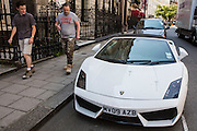 Two British builders walk past and admire a white Lamborghini car parked on Charles Street, Mayfair, central London, United Kingdom.  Mayfair is as a very affluent district of London.