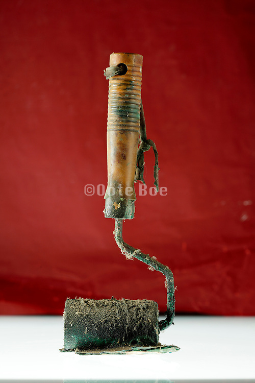 old paint roller with hardened paint and covered with dust