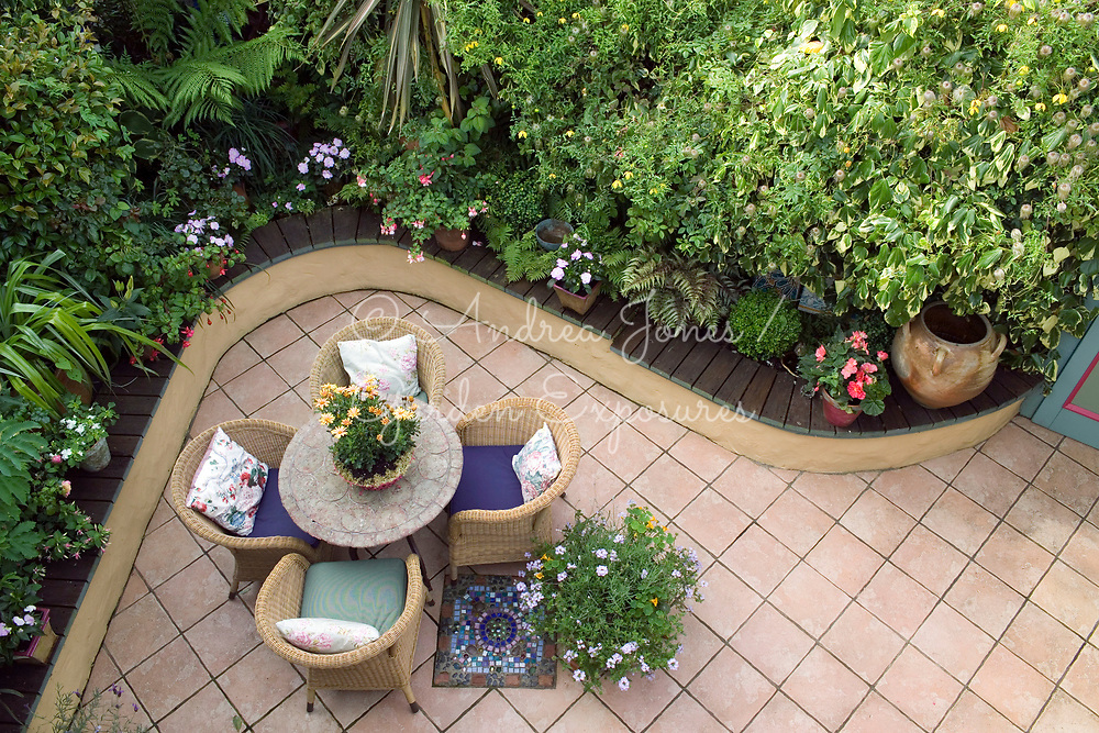 Enclosed and sheltered patio courtyard with wicker seating, mosaic tiles, ceramic table, raised beds and walls covered with climbing plants including Cleamtis tangutica, Jasminium officinale and Hedera varieties (ivy), flowering pots plants below