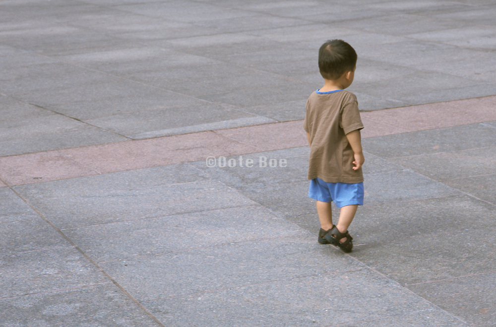 young child walking by himself