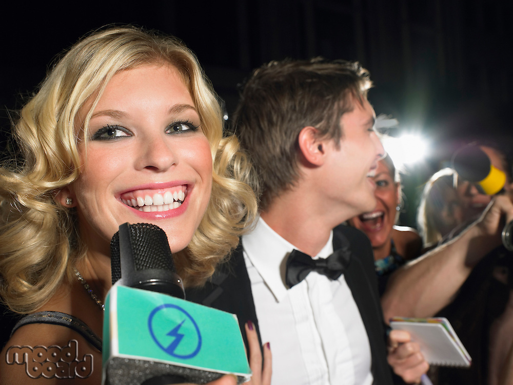 Woman talking into microphone man behind with paparazzi