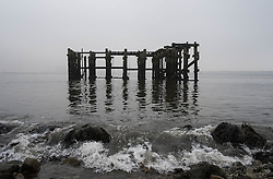 © Licensed to London News Pictures. <br /> 17/03/2015. <br /> <br /> South Gare, Teesside.<br /> <br /> The remains of an old jetty stands alone in the morning mist at low tide at an area known as South Gare on the mouth of the River Tees.<br /> <br /> Photo credit : Ian Forsyth/LNP