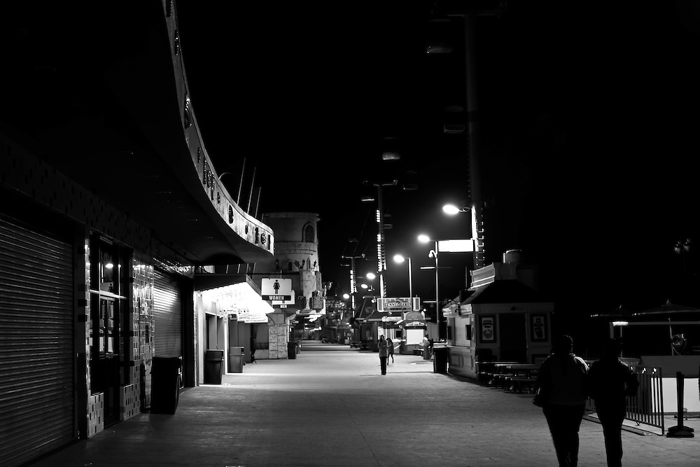 People walking Santa Cruz Boardwalk after dark, in Santa Cruz, CA. Copyright 2014 Reid McNally.