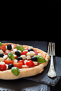 Fresh baked pizza with mozzarella cheese, black olives, cherry tomatoes and basil, on ardesia pieces isolated on black background.