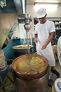 "Shigehisa Yonamuri operates a mixer that binds ingredients in the traditional ""kippan"" confectionery made from the kaabuchi citrus fruit at the Janaha Kippan-ten store in Naha, Okinawa, Japan on 27 June 2012. Today the Jahana family are the only people still making the traditional Kippan and Tougatsuke (which is made from ""Tougan"" winter melons) sweets that were served at the court of the Ryukyu kings over 300 years ago. Photo: Robert Gilhooly."