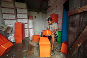Lukhi Ram, an employee at the biosand water filter factory, is preparing the containers which will sit in the top of the biosand filters. Water can be collected from any source and poured into the orange containers, from where gravity will pull it down through several layers, killing 99% of bacteria inthe process.