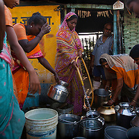 A women shares water from here well with villagers as part of a Government program to help ease tension from water scarcity in rural villages.