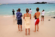 Galapagos Islands - Sunday, Dec 29 2002: Tourists watch sea lions, snorkellers and yachts from the beach.  (Photo by Peter Horrell / http://www.peterhorrell.com)
