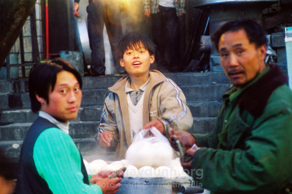 "China, Taiyuan, 2008. Sellers of ""baozi"", China's steamed dumpling,  are surprised by a stranger's interest. This vibrant area behind Yingze Dajie close to the train station was modernized, and is unrecognizable today."
