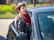 "05 APRIL 2020 - DES MOINES, IOWA:  LIAM MATTES, 7, waves his palm branch during a drive through Palm Sunday service sponsored by Luther Memorial Church on the campus of Grand View University in Des Moines. About 150 people attended the service. They remained in their cars while the ministers read a short passage from the Bible, handed out palms and blessed them. On Sunday, 05 April, Iowa reported 868 confirmed cases of the Novel Coronavirus (SARS-CoV-2) and COVID-19. There have been 22 deaths attributed to COVID-19 in Iowa. Restaurants, bars, movie theaters, places that draw crowds are closed until 30 April. The Governor has not ordered ""shelter in place"" but several Mayors, including the Mayor of Des Moines, have asked residents to stay in their homes for all but essential needs. People are being encouraged to practice ""social distancing"" and many businesses are requiring or encouraging employees to telecommute.       PHOTO BY JACK KURTZ"