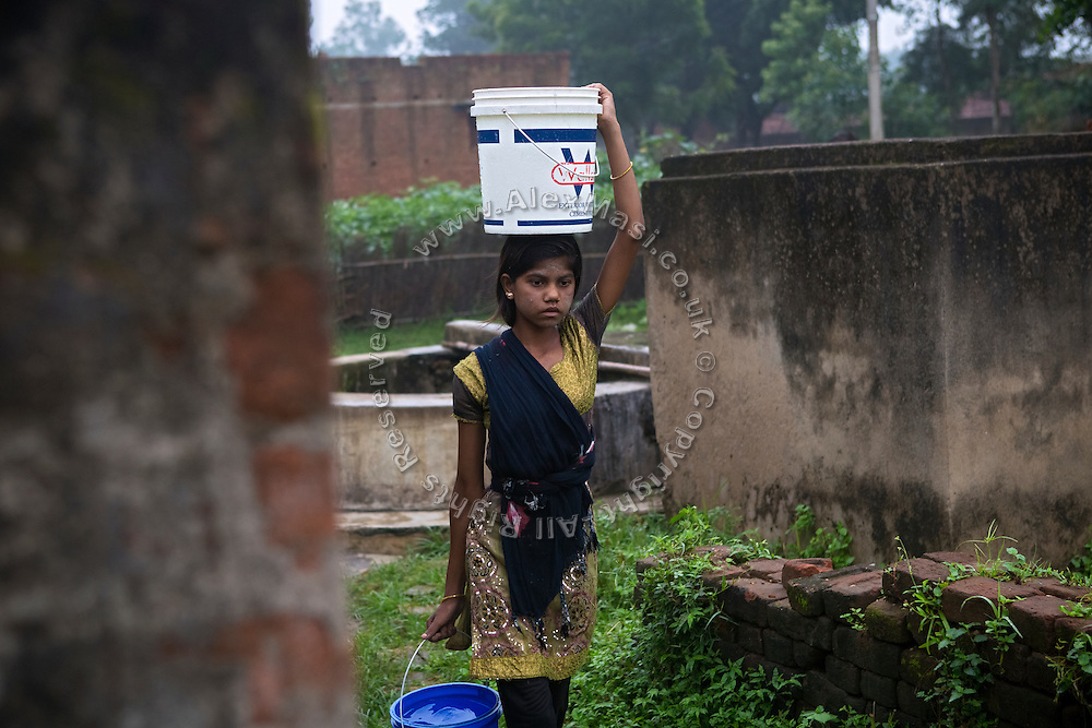 Tabasum Khatun, 14, is carrying two buckets of water to her home in Algunda village, pop. 1000, Giridih District, rural Jharkhand, India.