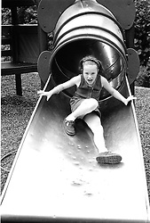 Young girl playing on tube slide in adventure playground,