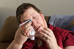 1/27/15 11:57:19 AM -- Louisa, KY, U.S.A  -- Cheryl Castle eyes water after she uses the remote monitor and wand to collect data from the neurostimulator. Castle is a recent recipient of the high-tech device, can now do many tasks she was unable to do when her epileptic seizures became more severe and more frequent. Now she's getting back to a normal life.<br /> <br />  --    Photo by Jonathan Palmer, Freelance